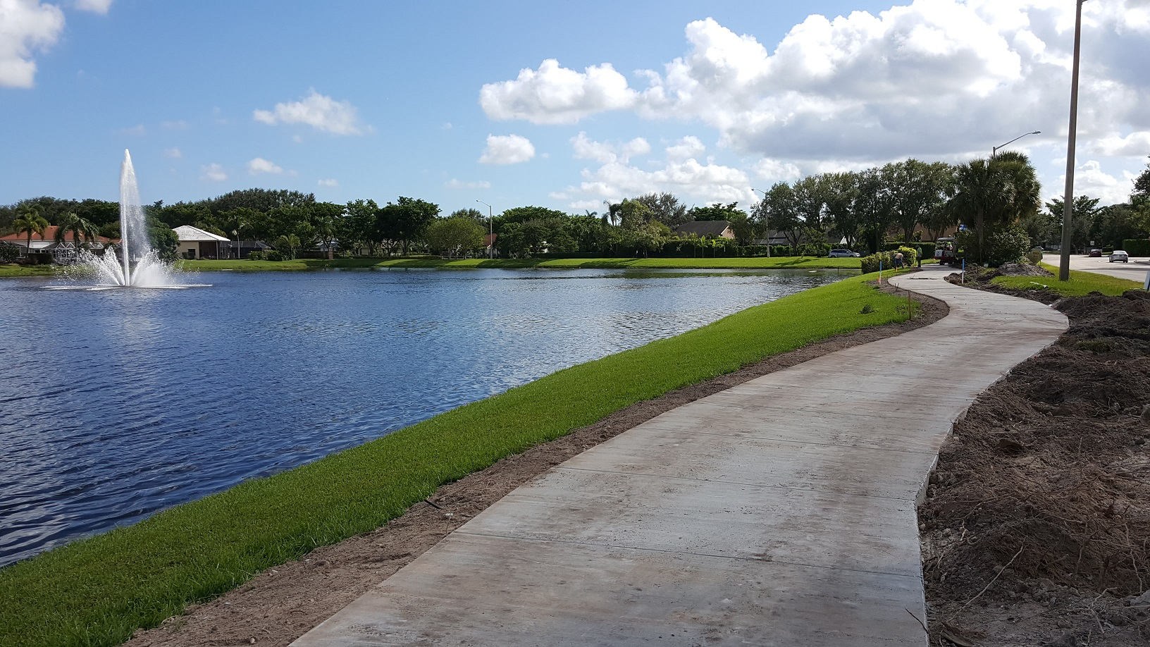 Paved walkway with lake fountain in distance